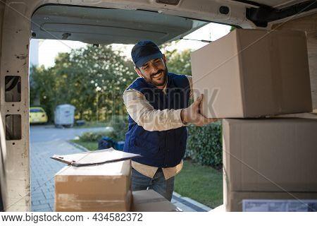 Deliveryman Arranging Packages In His Van Before Delivering.