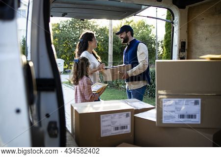 Deliveryman Delivering Packages To The Clients In Front Of The House.