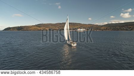Slow motion of yacht reflection at sea gulf aerial. Alone sail boat reflect at ocean bay. Racing sailboat at Brodick Harbor, Scotland, Europe. Luxury vessel at summer cruise. Cinematic soft light shot