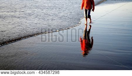 Young child wearing a red jacket playing on the beach of the ocean with waves rolling in