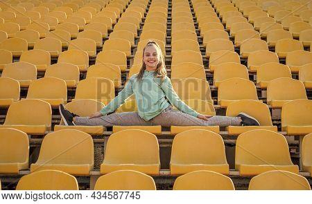 Happy Girl Gymnast Do Splits Stretching Legs On Stadium Seats, Gymnastics