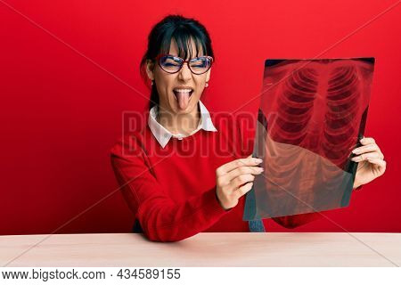 Young brunette woman with bangs holding chest radiography sticking tongue out happy with funny expression.