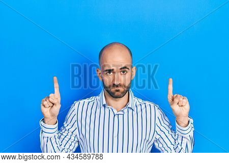 Young bald man pointing up with fingers skeptic and nervous, frowning upset because of problem. negative person.