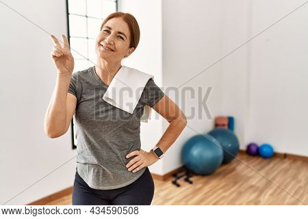 Middle age woman wearing sporty look training at the gym room smiling looking to the camera showing fingers doing victory sign. number two.