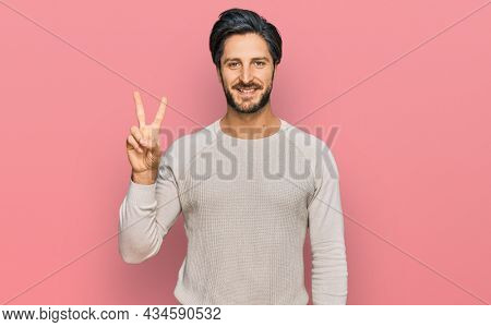 Young hispanic man wearing casual clothes smiling with happy face winking at the camera doing victory sign. number two.