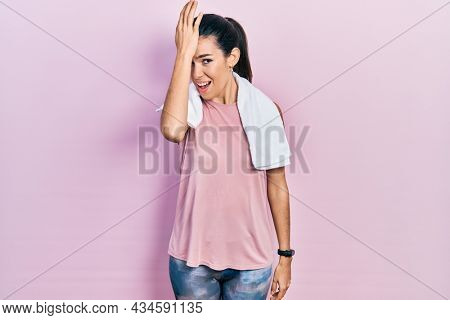 Young brunette woman wearing sportswear and towel surprised with hand on head for mistake, remember error. forgot, bad memory concept.