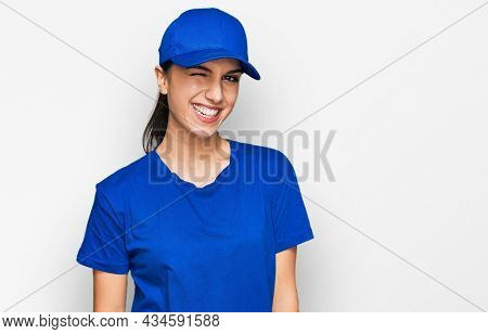 Young hispanic girl wearing delivery courier uniform winking looking at the camera with sexy expression, cheerful and happy face.
