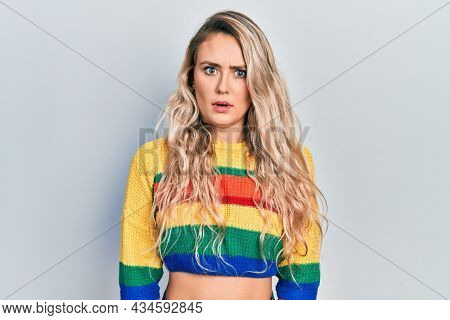 Beautiful young blonde woman wearing colored sweater in shock face, looking skeptical and sarcastic, surprised with open mouth