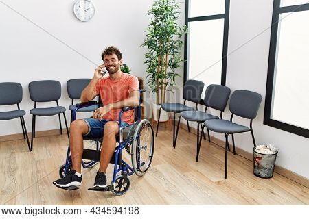 Young hispanic man talking on the smartphone sitting on wheelchair at clinic waiting room.