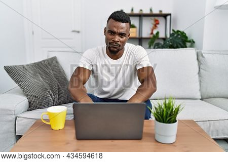 Young african man using laptop at home skeptic and nervous, frowning upset because of problem. negative person.