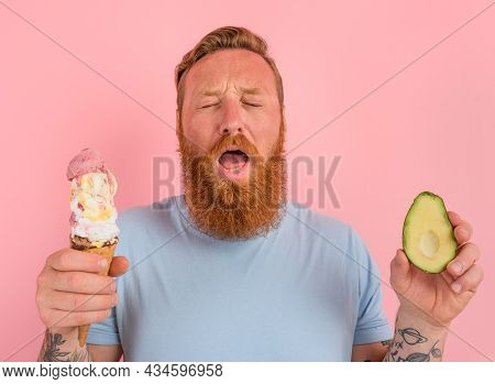 Thoughtful Man With Beard And Tattoos Is Undecided If To Eat An Icecream Or An Avocado