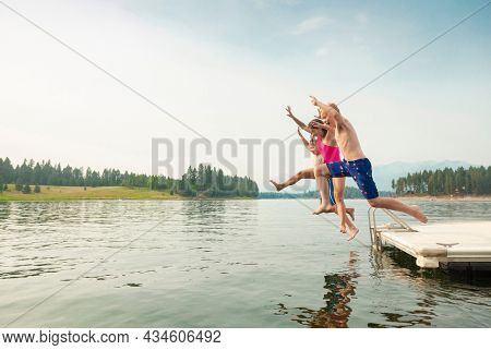 Group of teenage kids jumping off the dock into the lake together during a fun summer vacation.