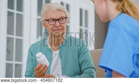 Senior woman with glasses holds pills bottle in room