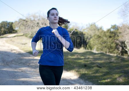 Centered close up of woman jogging outside, facing right