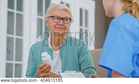 Senior patient woman with glasses holds pills bottle listening to doctor explanations in room