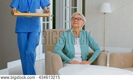 Caretaker in blue uniform carries tray with breakfast to mature grey haired lady sitting in armchair at table