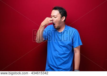 Young Asian Man Smelling Something Stinky And Disgusting