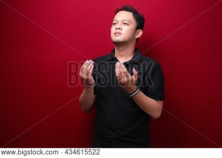 Calm Spiritual Handsome Asian Guy Praying With Closed Eyes. Serious Peaceful Young Man With Joining