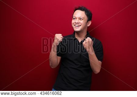 Happy Excited And Smiling Young Asian Man Raising His Arm Up To Celebrate Success Or Achievement.