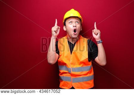 Shock Young Asian Man Worker Is Surprised And Shouting Wow With Pointing Above With His Hand Isolate
