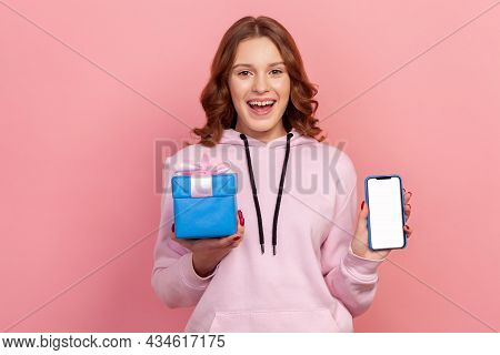 Portrait Of Happy Curly-haired Teenage Girl In Hoodie Holding Smartphone And Wrapped Gift Box, Smili