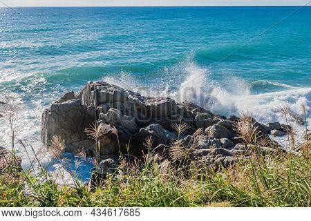 Waves Crashing To Shore Against Large Boulders
