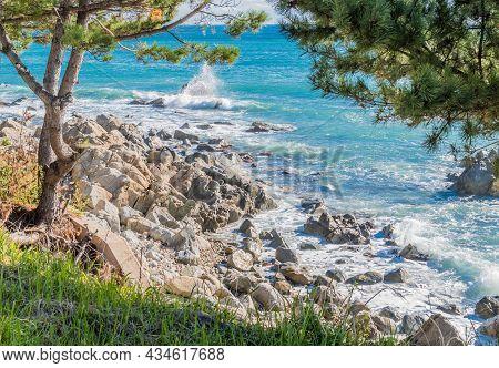 Waves Crashing To Shore Among Large Boulders