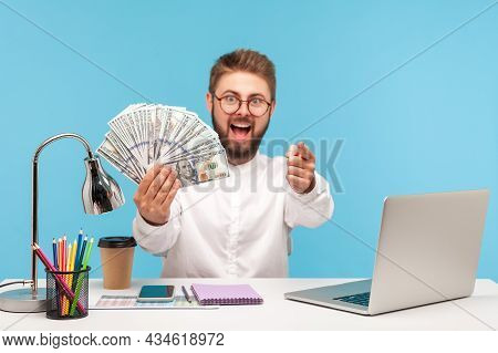 Extremely Positive Rich Man With Beard Holding Fan Of Dollars Pointing Finger At You, Sitting At Wor