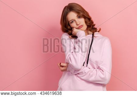Portrait Of Upset Bored Teen Girl In Hoodie Leaning On Hand And Expressing Apathy With Dull Look, Fe