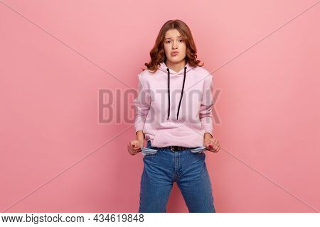 Portrait Of Upset Poor Student Girl In Hoodie And Jeans Turning Out Empty Pockets, Showing No Money