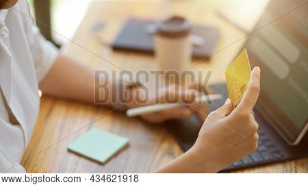 Close-up Of Woman Holding A Credit Card In Front Of A Portable Tablet