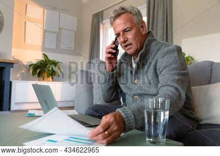 Focused caucasian senior man sitting on sofa, doing paperwork, making call and using laptop. active retirement lifestyle at home.