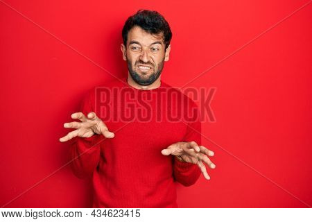 Handsome man with beard wearing casual red sweater disgusted expression, displeased and fearful doing disgust face because aversion reaction.