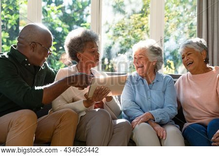 Three happy diverse senior woman and african american male friend sitting on sofa and using tablet. retirement lifestyle relaxing at home with technology.