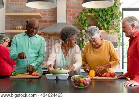 Group of happy diverse senior male and female friends cooking together at home. cooking and socialising with friends at home.