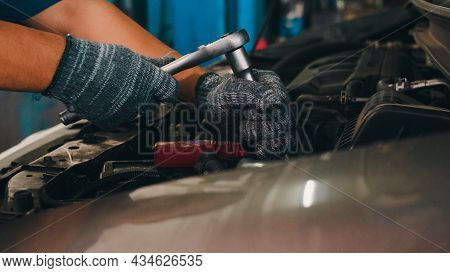 Professional Car Mechanic Screwing Details Of Car Engine On Lifted Automobile At Repair Service Stat