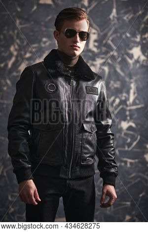 Attractive young man in a black leather jacket and black sunglasses posing in a grunge background. Man's fashion.