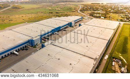 Aerial Shot Of Industrial Warehouse. Loading Hub And Many Trucks With Cargo Trailers. Aerial View Of