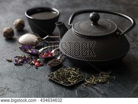 Chinese Teapot With Cup And Infuser With Various Tea On Black. Rose Buds,blue Mallow Flowers,green A