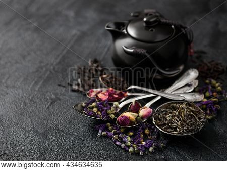 Teapot With Spoons With Various Tea On Black. Rose Buds,blue Mallow Flowers,green And Black Loose Te