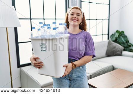 Young redhead woman holding recycling wastebasket with plastic bottles with a happy and cool smile on face. lucky person.