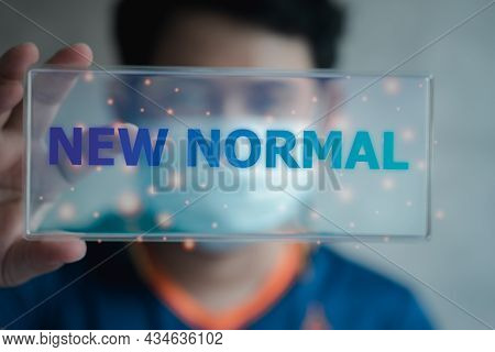Hand Flipping A Glass Tag For New Normal Wording. The World Is Changing To Balance It Into New Norma