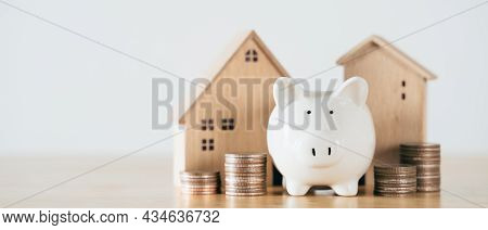 Wooden House With White Piggy Bank And Stacking Coins On Wooden Table. Saving Money For Buying House