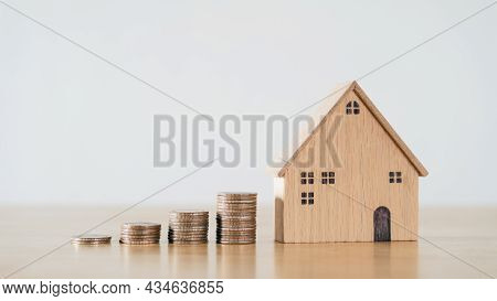 Wooden House And Stacking Coins On Wooden Table. Saving Money For Buying House, Financial Plan Home