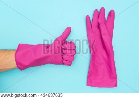 Man In A Protective Rubber Glove. Symbol Like. Rubber Gloves For Cleaning On A Blue Background. Flat