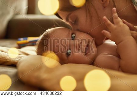 Close Up Gentle Kiss Of Affectionate Mother. Smiling Baby Looking At Camera, Feeling Mothers Kiss On