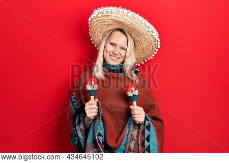 Beautiful caucasian blonde woman wearing festive mexican poncho and maracas winking looking at the camera with sexy expression, cheerful and happy face.
