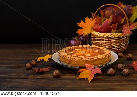 Autumn Background With Pumpkin Cake, Maple Leaves, Aples And Acorns. Copy Space