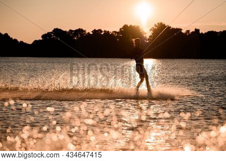 Beautiful View Of Dark Silhouette Of Active Male Rider Holds Rope Riding On Wakeboard On Water Surfa