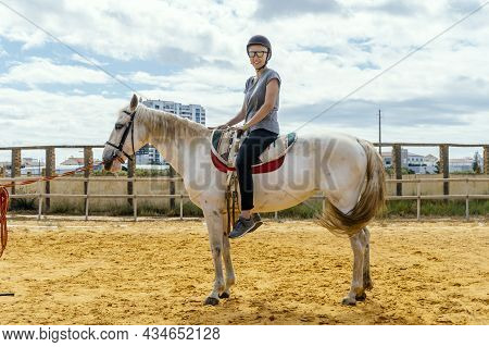 A Woman Taking Horse Riding Lessons In A Paddock